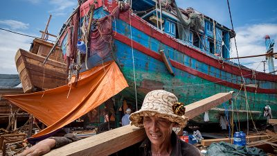 A worker carries a piece of wood to build an wooden fishing boat with the DNa 90152 on the background, the boat that was rammed by a Chinese vessel in late May 2014, on August 29, 2016 in Danang, Vietnam. Vietnam, known to be among the most vocal critics on China's territorial claims, continues to denounce the dispute over the South China Sea with a history of violent clashes since 1974. In recent years, the fierce standoffs continue between the two countries over fishery, oil and gas reserves which had prompted massive riots in Hanoi 2 years ago which were followed by collisions between Vietnamese and Chinese ships. Local media reported 4000 boats had run into accidents involving foreign boats over the past 2 years while thousands of Vietnamese fishermen claim their fishing boats have been rammed and sank by the Chinese. As Vietnamese fishermen persist in carrying out their fishing operations, their main defense for them is to join forces at sea to ensure safety while replacing the old boats with new ones which are bigger and more powerful with help from government loans to upgrade their boats.